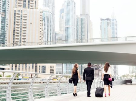 office workers walking beside a river in a city