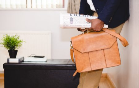 a businessman carrying a briefcase and newspaper