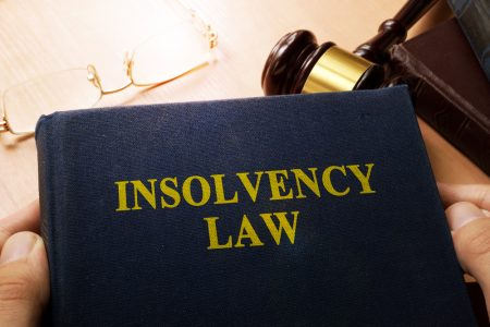 Insolvency law book on a desk over a gavel