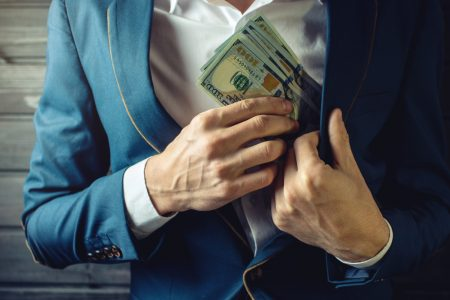 Man putting money from undisclosed commission inside his suit's pocket.